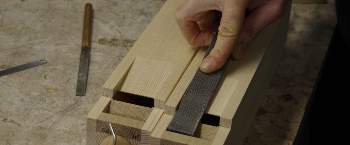 Ein Intonateur feilt die Kernspalten in die Kerne zweier Holzgedacktpfeifen.