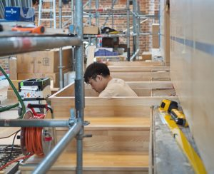 Das Podest vor der Orgel wird aufgebaut und genau an den Boden angepasst