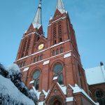 Blick von unten auf das Hauptportal der Kirche mit den beiden Kirchtürmen. Dächer und Umgebung ist schneebedeckt.