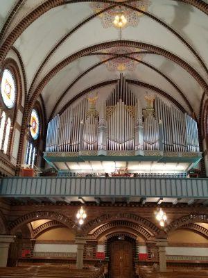 Blick aus dem Kirchenschiff auf die Orgelempore, die Orgel fült die Kirche fast in kompletter Breite, die Prospektpfeifen glänzen im Sonnenlicht