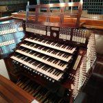 Orgelspieltisch in dunkelrotem Mahagoni. Vier Manuale, Registerwippen rechts, links und über den Manualen angeordnet.