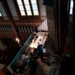 Blick aus dem Inneren der Orgel auf die Orgelgallerie. Ein Mitarbeiter reinigt und repariert eine Pfeife des Prospekt-Mittelfeldes